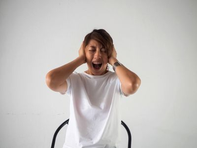 A woman covers her ears while screaming