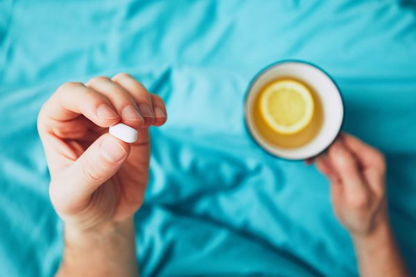man with a vitamin supplement and cup of lemon tea