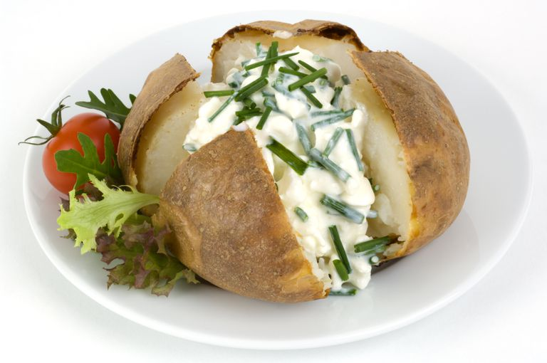 Jacket potato with cottage cheese and chives, close up