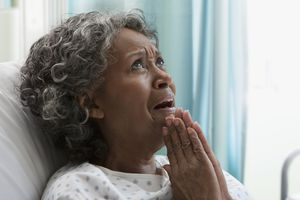Worried African hospital patient with hands clasped