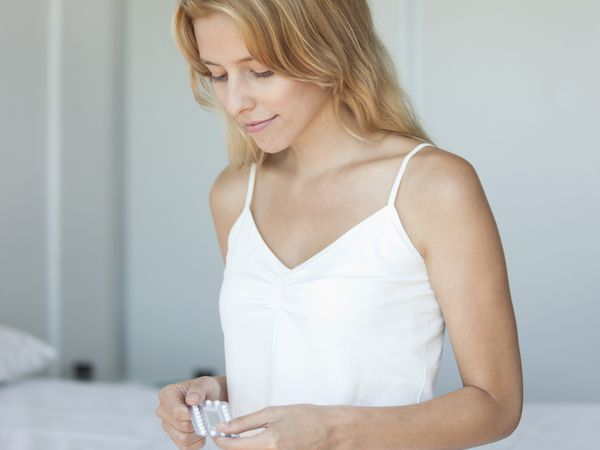 A young woman holding her birth control