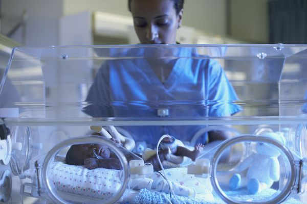 African American nurse examining baby in hospital incubator