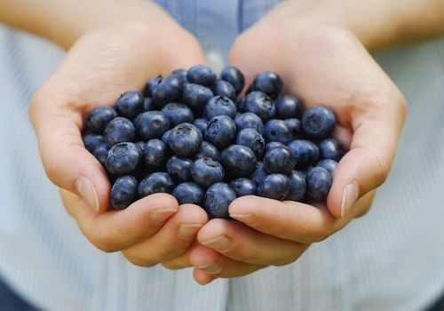 Woman with a handful of blueberries