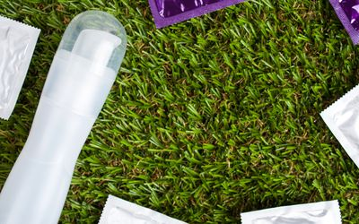 Condoms and erotic lubrication lie on the green artificial grass