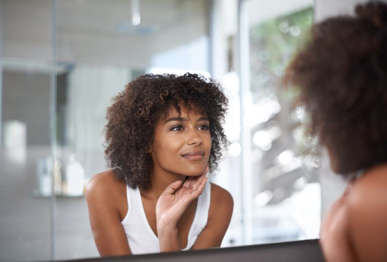 black woman looking in mirror