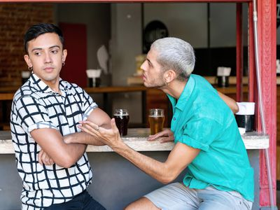 A young, gay couple sits at a restaurant counter