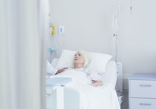 Doctor talking to a worried senior female patient in a hospital bed