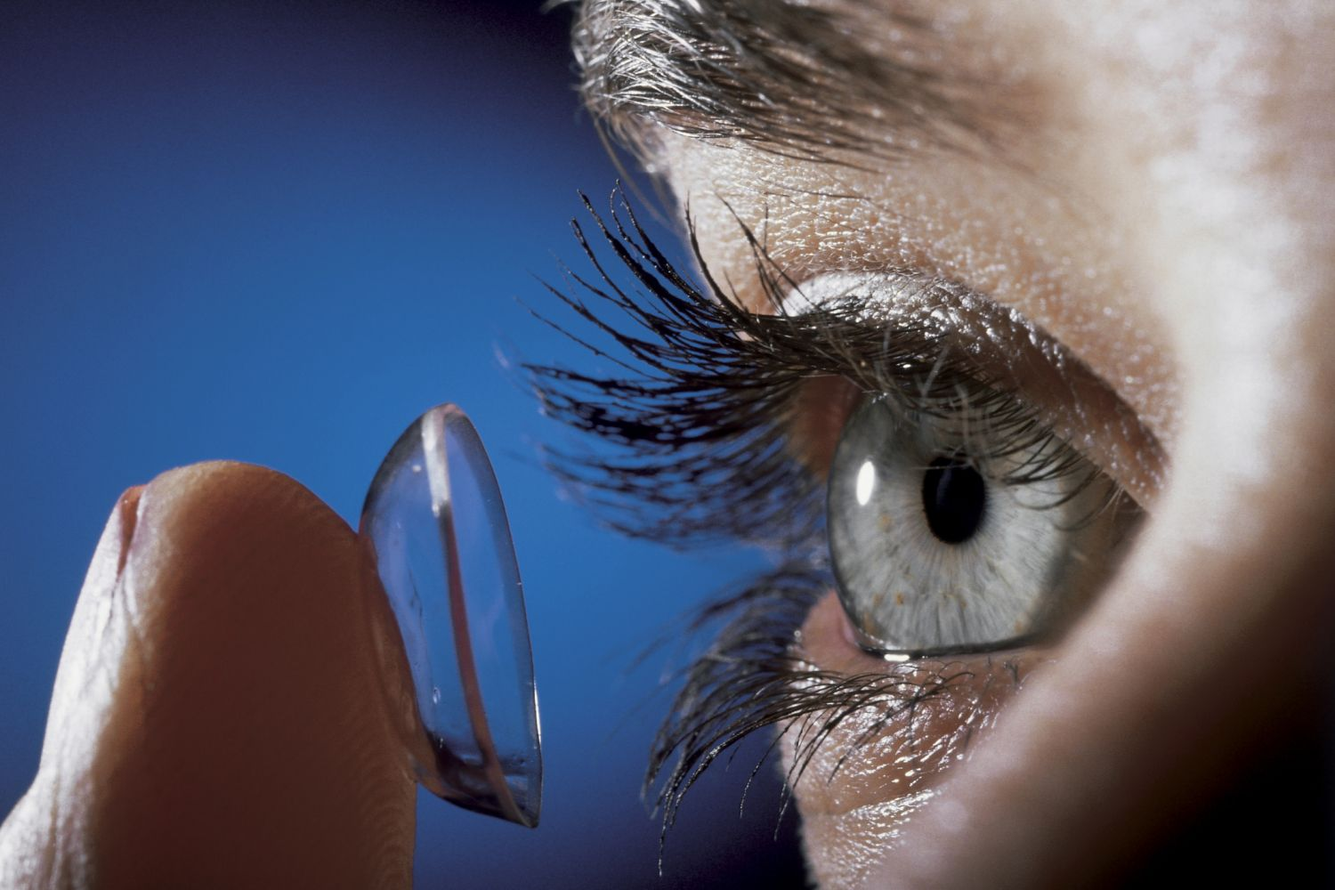 Close up of a person inserting a contact lens