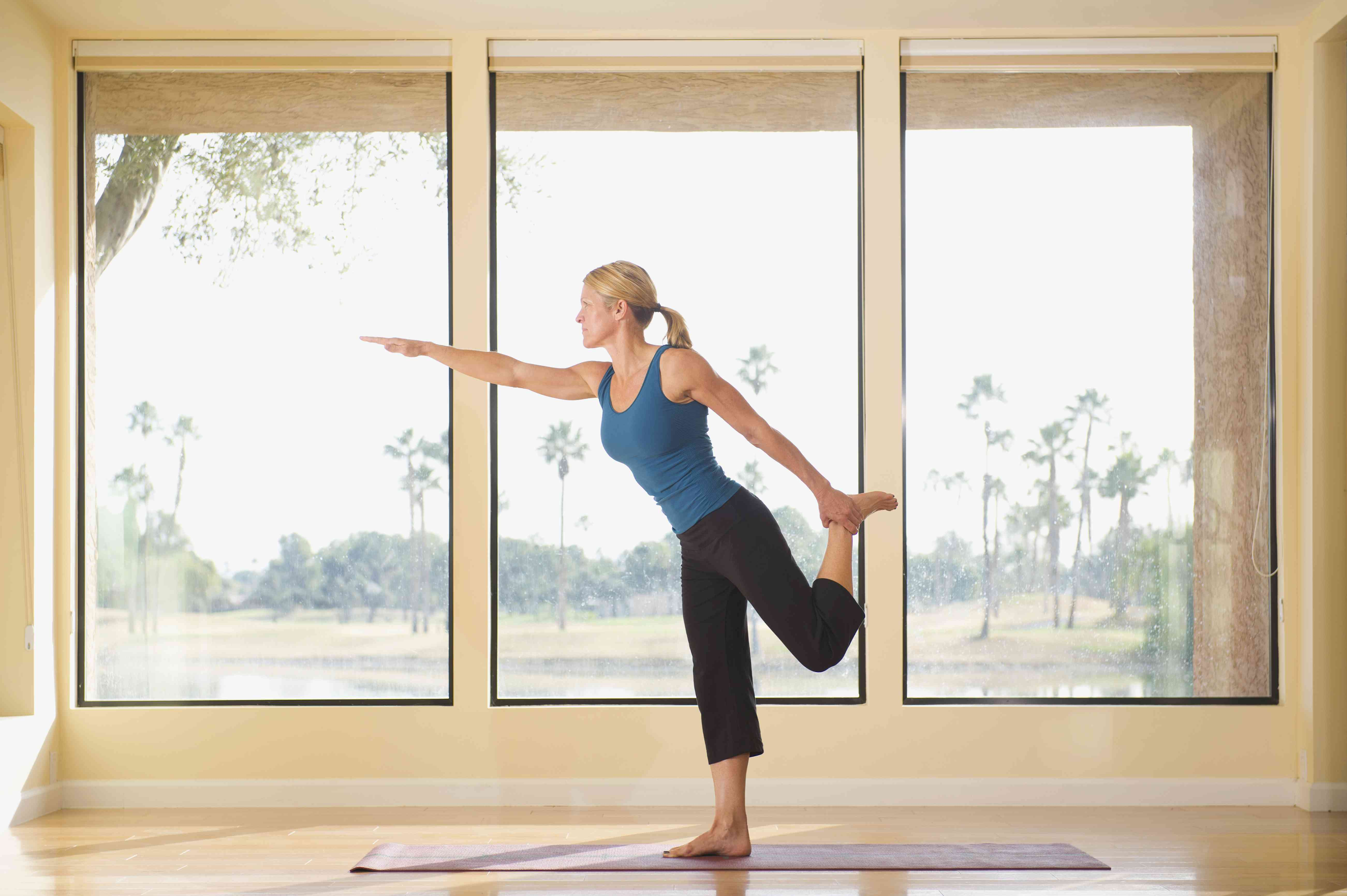 A woman performing yoga balance exercises near a large window