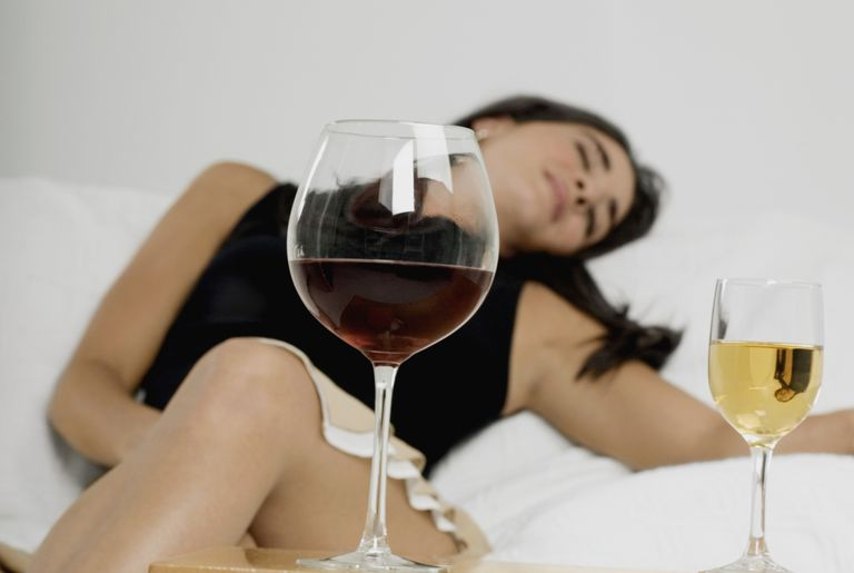 Young woman sleeping with wineglasses in front of her