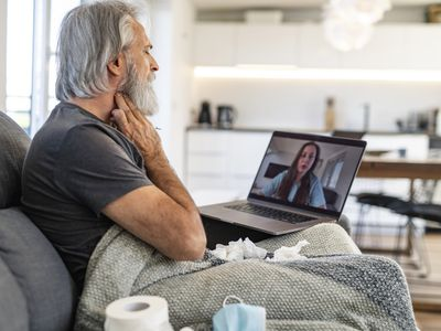 unwell mature man discussing symptoms on medical video call