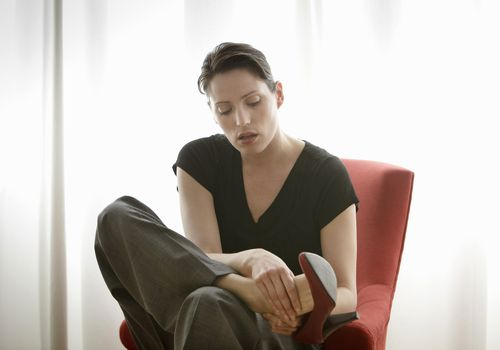 A woman rubbing her sore feet