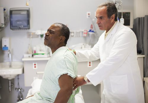 Man experiencing pain when being examined at hospital.