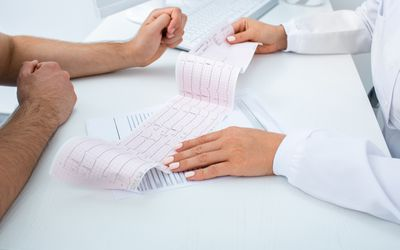 Doctor analyzes the electrocardiogram results, close-up. Diagnosis of arrhythmia, heart rate and heart disease