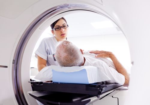 older man receiving Radiotherapy with woman nurse standing by