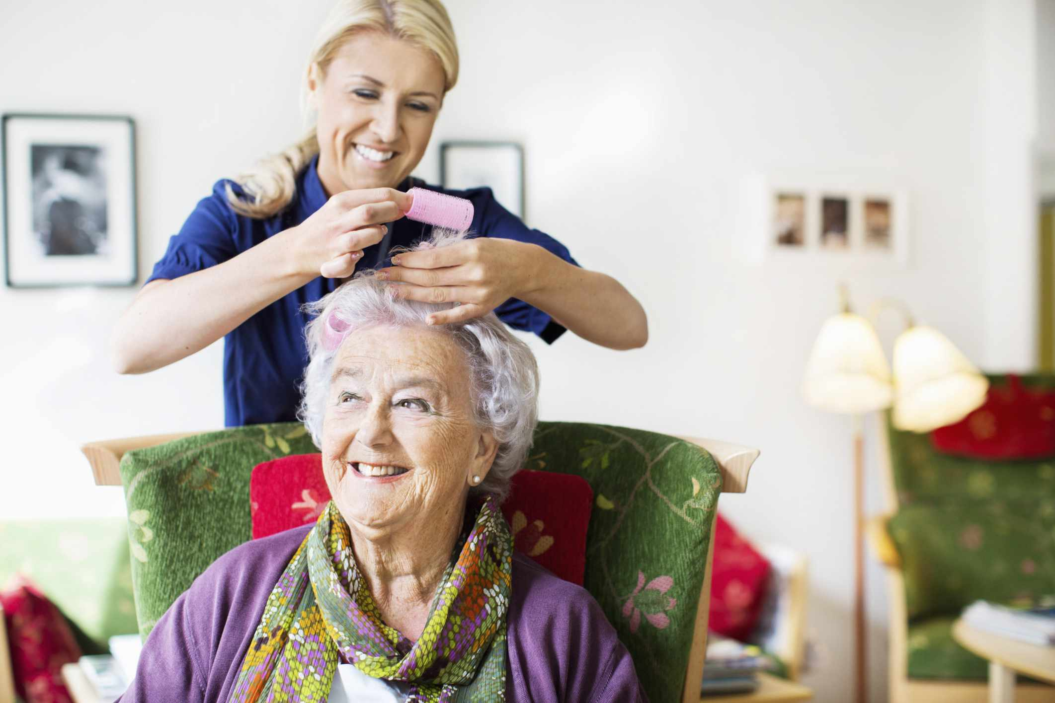 Woman styling a mature woman's hair in a home setting, both smiling