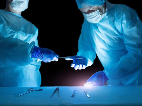 surgeons holding surgical laser in operating room