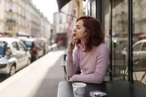 Woman smoking in outdoor cafe