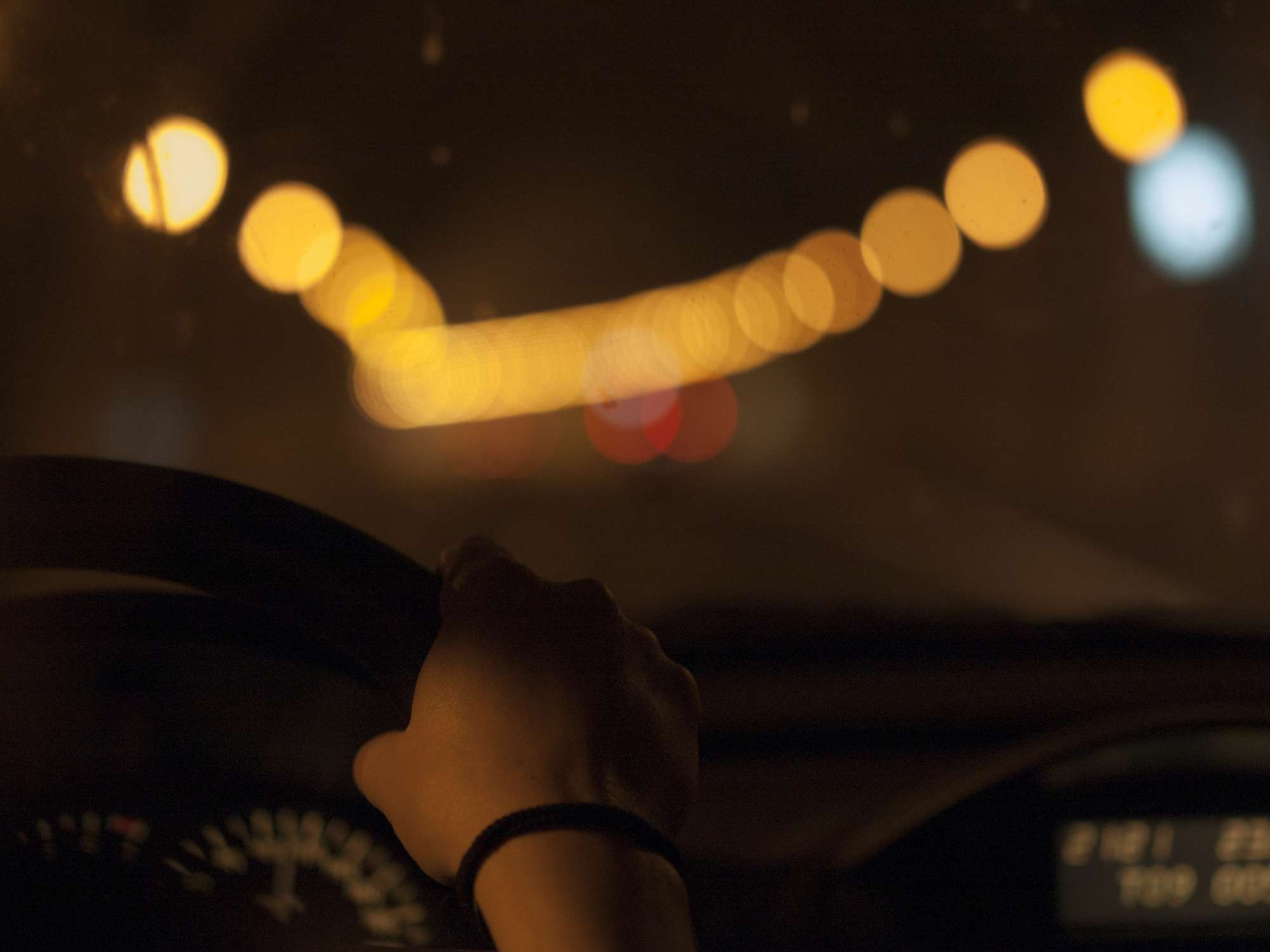 Woman driving a car with dirty windshield at night inside a tunnel. Detail of hand on the wheel in the dark, surrounded by colored and blur lights