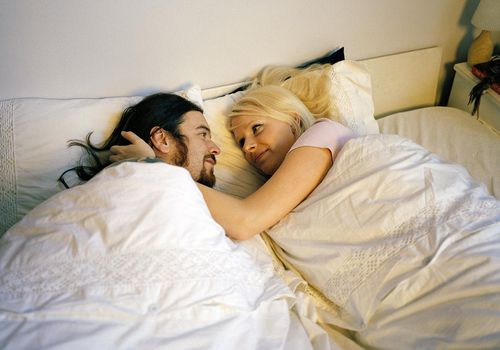 Couple embracing in bed, looking at each other
