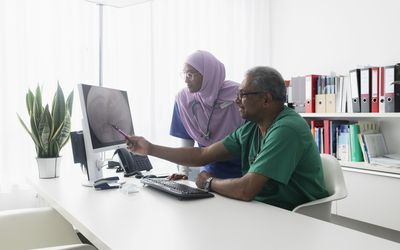 Two gastroenterologists discuss images from an endoscopy.
