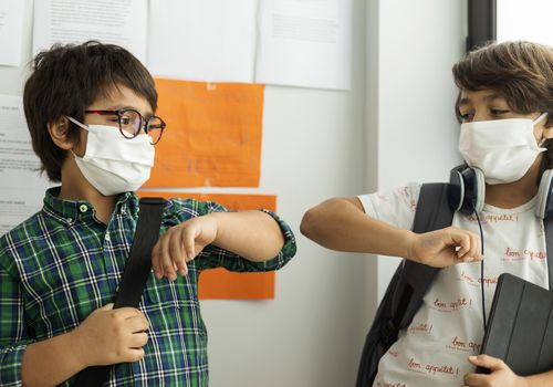 Boys wearing masks give each other elbow bump