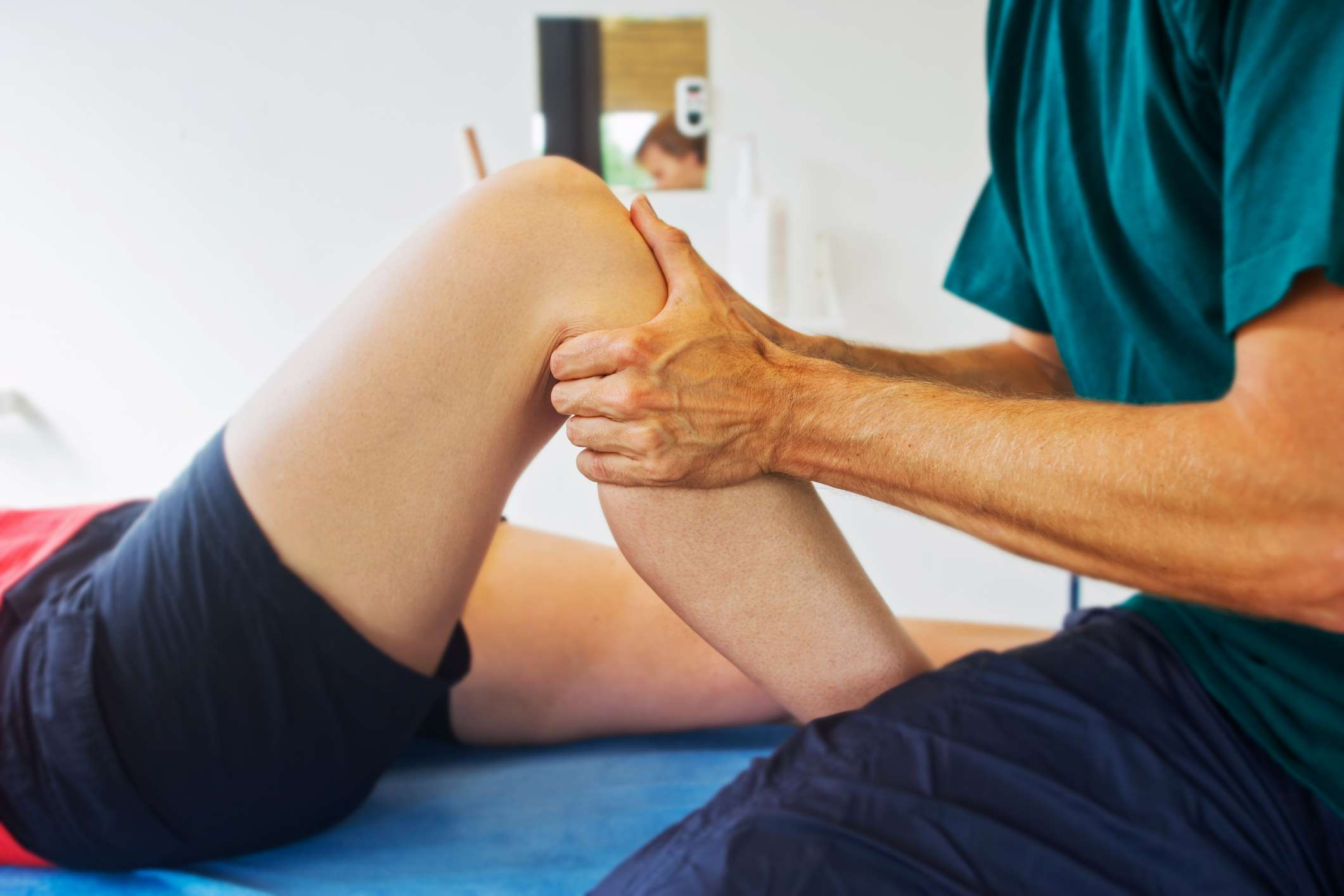 Physical therapist massaging patient's knee