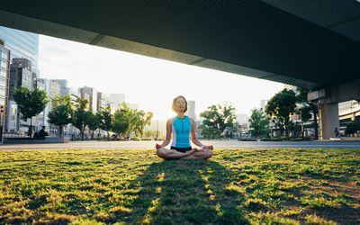 Woman meditating under bridge outside