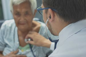 Doctor listening to his patients hearbeat