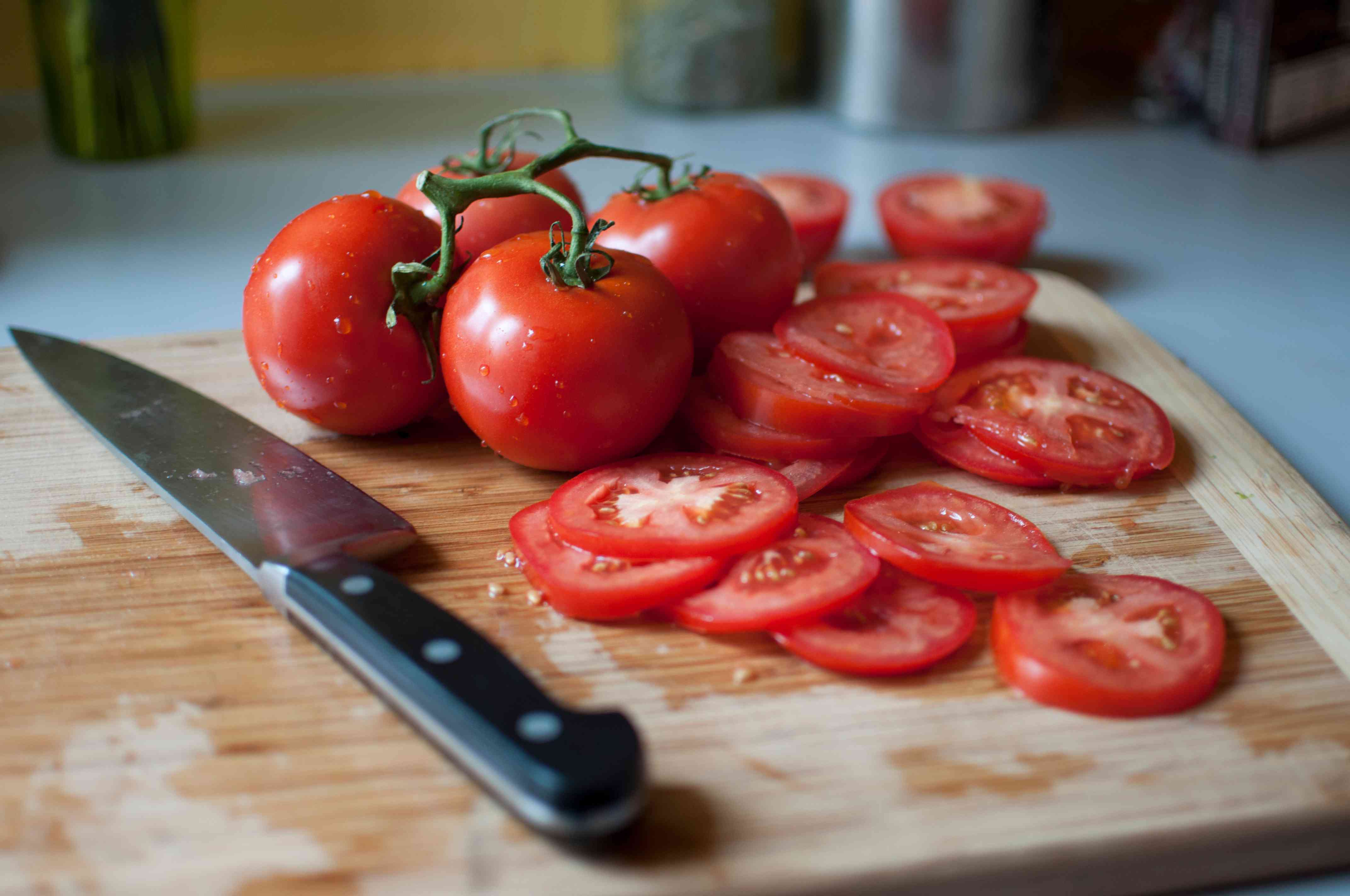 Whole and sliced tomatoes on a cutting board alongside a knife