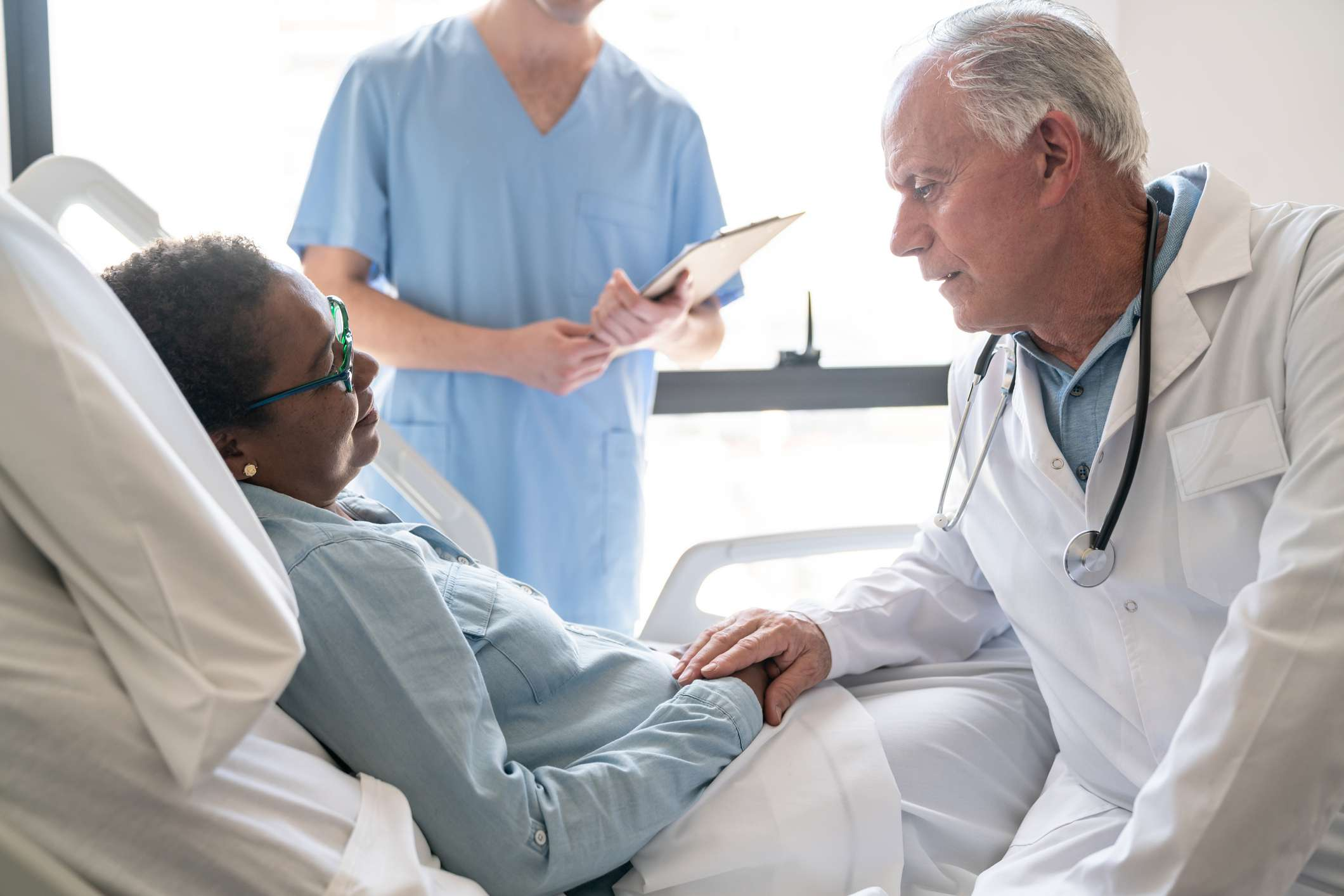 Friendly doctor comforting a black female patient lying down on hospital bed