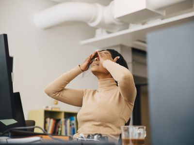 Tired woman sitting at a computer with hands over her eyes