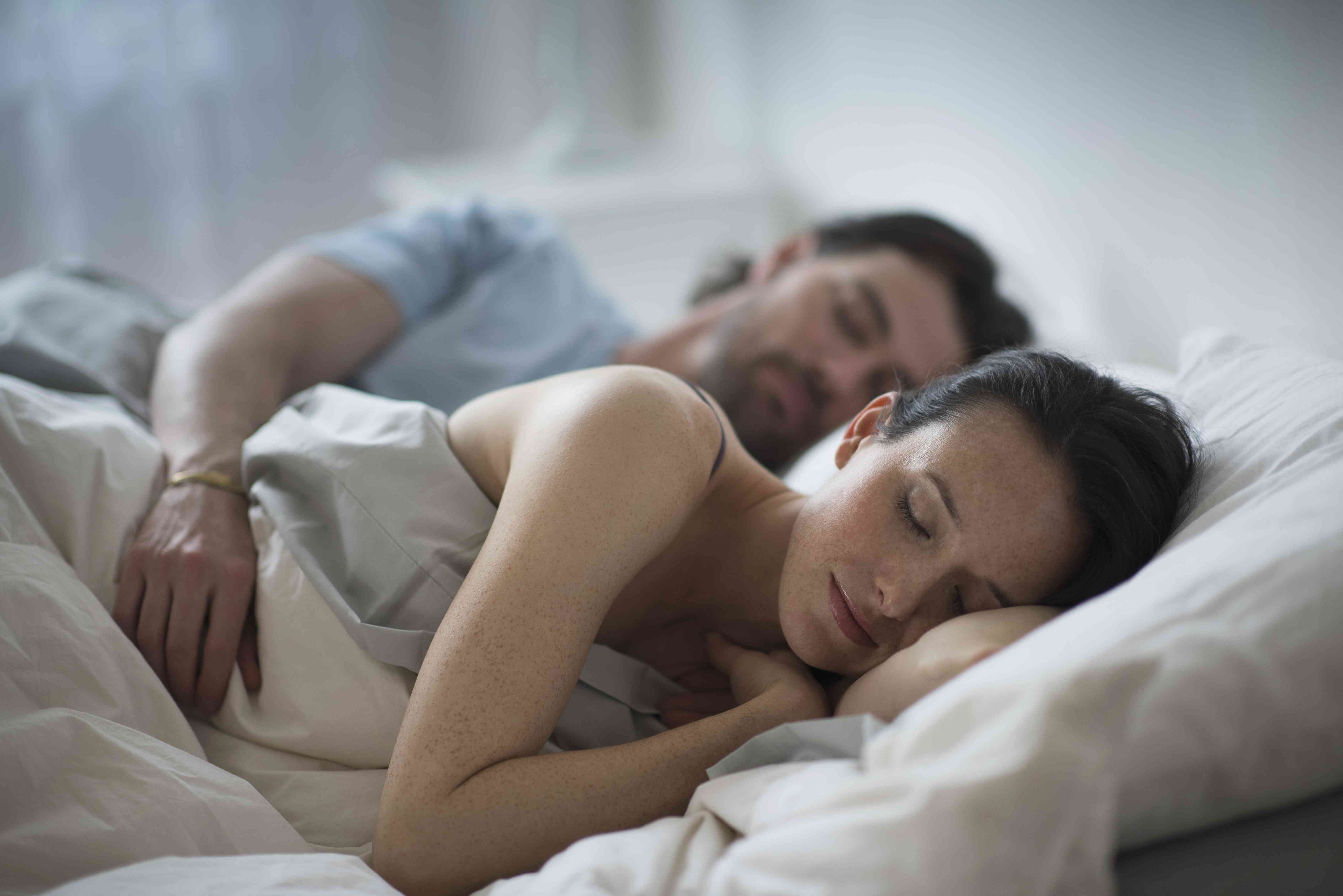 A couple sleeping together in bed at night