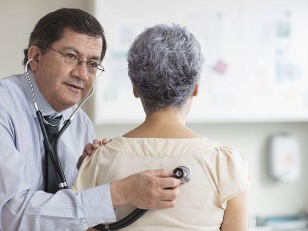 Hispanic doctor listening to back of patient with stethoscope