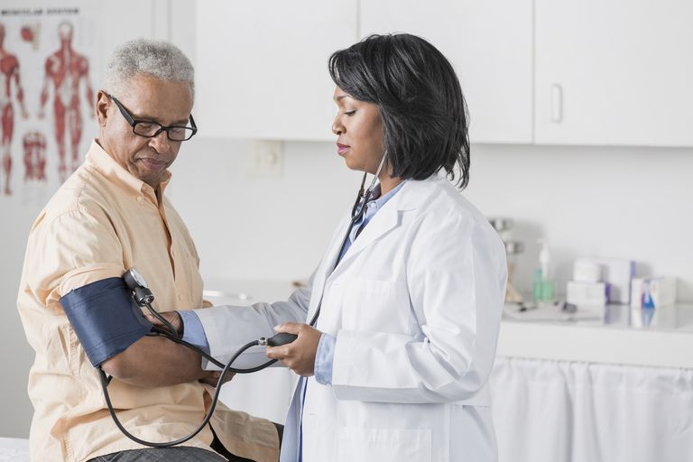 African American doctor checking senior man's blood pressure