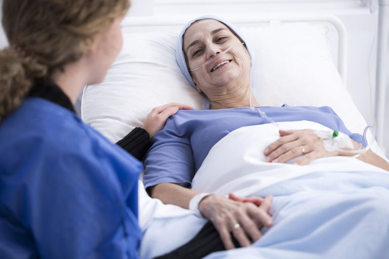 Cancer patient in bed holding hands with caregiver