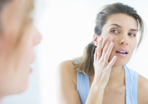 woman looking at skin in mirror