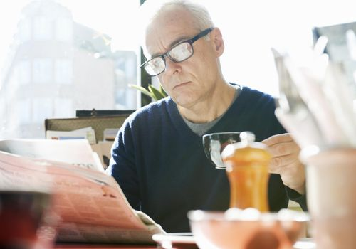Mature man reading newspaper in cafe