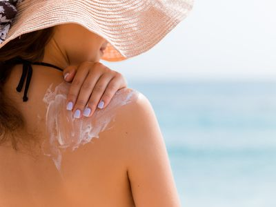 Young girl in straw hat is applying sunscreen on her back to protect her skin