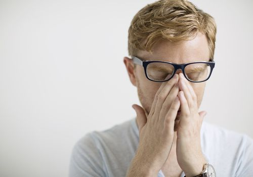 man holding his nose with sinus pain