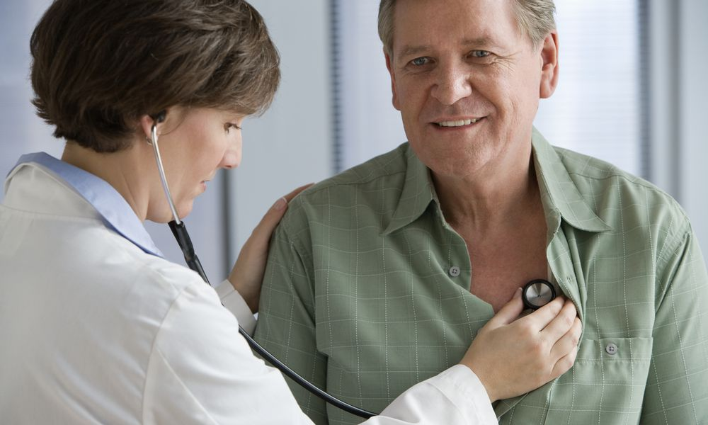 Female doctor listening to male patient's heart with stethoscope