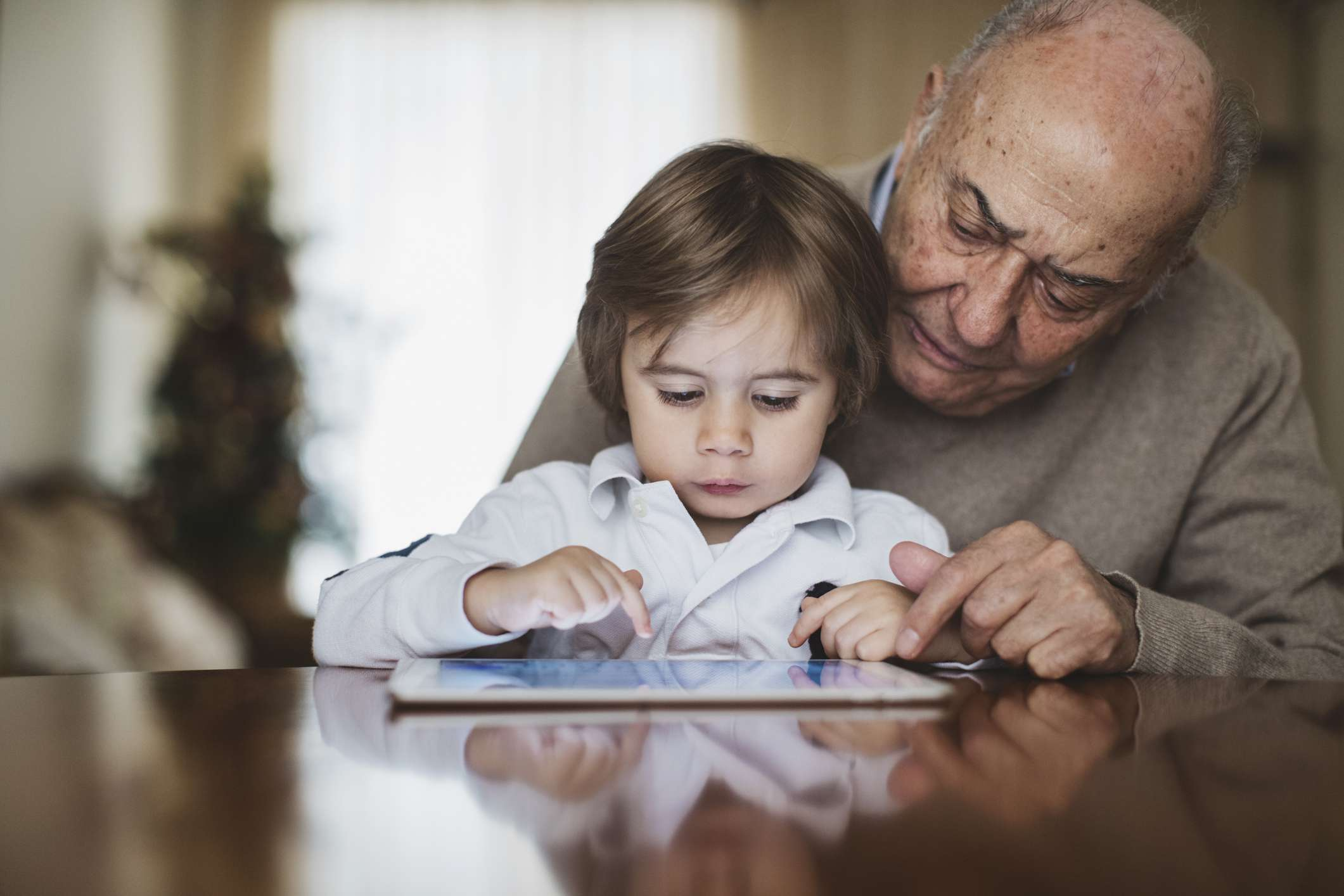 An older man reading his is grandson