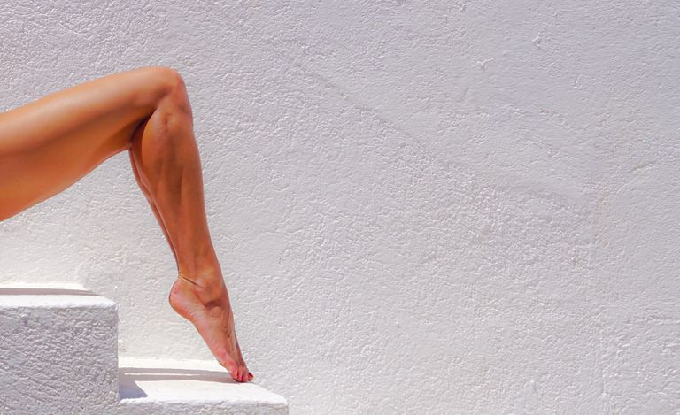 A woman's bent leg is shown, the toe pointed to show off the calf muscles.