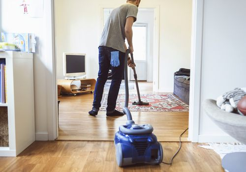Rear view of man vacuuming carpet