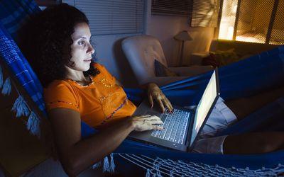 Woman using laptop computer in dark room