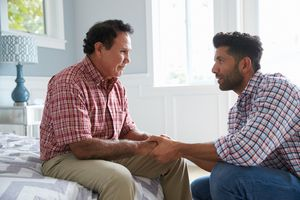 Adult Son Comforting Father Suffering With Dementia - stock photo