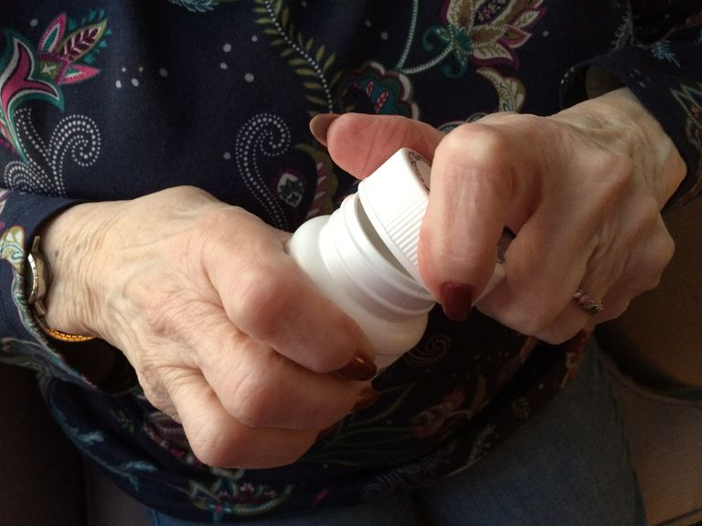 woman with arthritis trying to open pill bottle