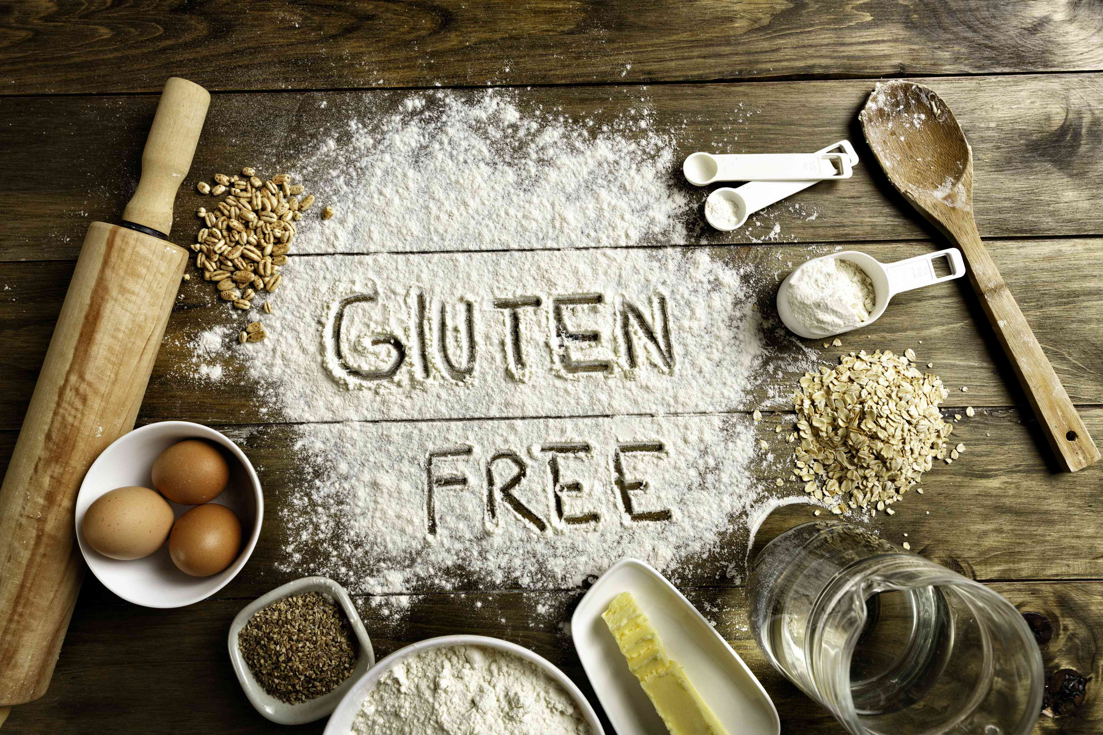 Gluten-free bread ingredients and utensils on wood frame background