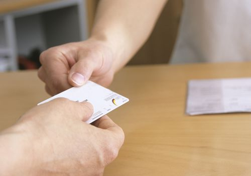 A patient presents a health insurance card.