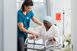 Woman with cancer being assisted by a nurse.